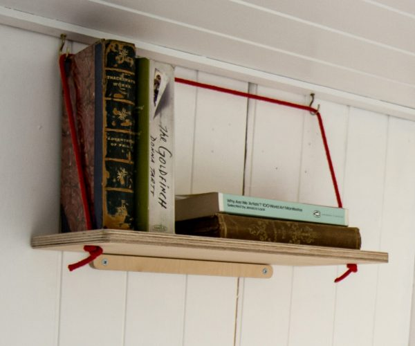 Everything Goes - Hang Shelf - storing books on a sloped boat wall. Birch ply with red rope.