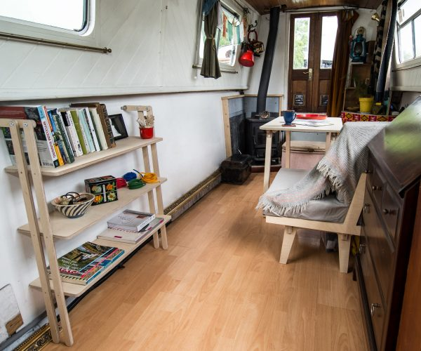 Everything Goes - Slant shelving for boats and angled walls. Shown here, installed on a narrowboat against an angled wall, displaying books, bowls, tins, photo and display items.